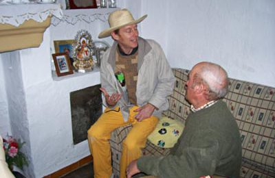 Richard interviews Don Pedro in his living room next to the very first face, now cut out and cemented next to the fireplace