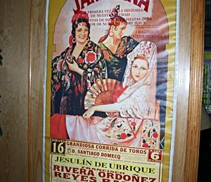 A poster of women in Andalusian dress announcing a bullfight on the wall of the restaurant.